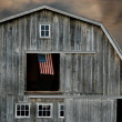 Old barn at sunset with flag — Stock Photo #11097815