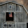 Stock Photo: Old barn at sunset with flag