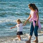 mor och barn på en strand — Stockfoto