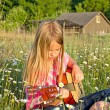 Girl in field with guitar — Stock Photo #11114878