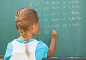 Writing lines on chalkboard — Stock Photo