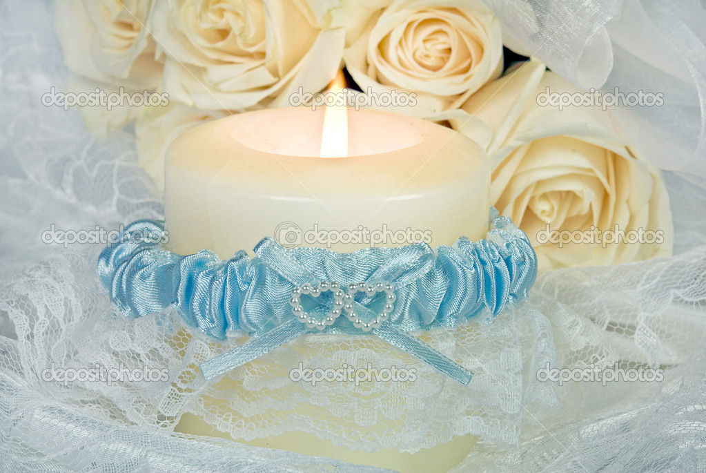 Blue satin garter wrapped around a white glowing cande with lace. — Lizenzfreies Foto #11134994