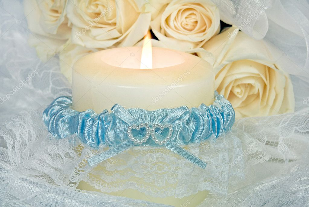 Blue satin garter wrapped around a white glowing cande with lace. — Zdjęcie stockowe #11134994