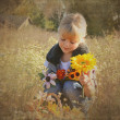 Sweet child in autumn field — Stock Photo