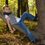 Little girl on tree branch — Stock Photo