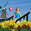 Girl with balloon by windmill — Stock Photo