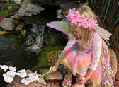 Child painting an orchid — Stock Photo