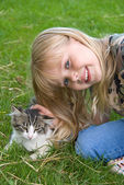 Child petting a kitten — Stock Photo