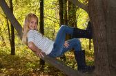 Girl reclining on tree limb — Stock Photo