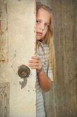 Girl peeking around door — Stock Photo