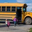 Kids getting off school bus — Stock Photo