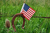 Horseshoe and flag on barb wire — Stock Photo