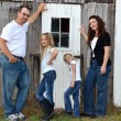 Family posing by an old barn — Stockfoto