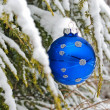 Christmas ornament on snowy pine - Stockfoto