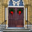 Christmas wreaths on church doors — Stock Photo