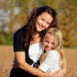 Mother hugging daughter — Photo