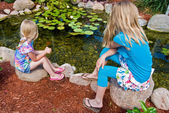 Girls by koi pond — Stock Photo