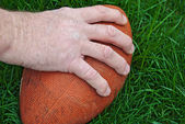 Man's hand on football — Stockfoto