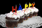 Birthday candles on cupcakes — Stock Photo