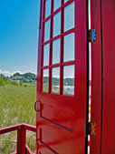 Red door opened to beach scene — Stock Photo