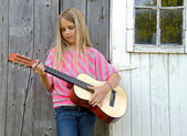 Young girl playing guitar — Stock Photo