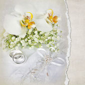 Wedding rings and orchid bouquet — Stock Photo