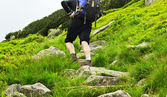 View of a trekker with a backpack walking up a hill — Stock Photo
