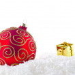 A red and gold christmass decoration on snow — Stock Photo