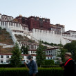 Tibetan turning prayer wheels in front of Potala Palace - Stock Photo