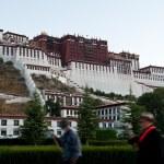 Tibetan turning prayer wheels in front of Potala Palace — Stock Photo