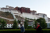 Tibetan turning prayer wheels in front of Potala Palace — Stock Photo