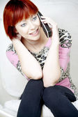 Młoda kobieta siedzi i rozmowy przez telefon — Zdjęcie stockowe