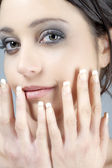 Portrait of young woman covering face with hands — Stock Photo