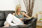 Young woman relaxing on sofa — Stock Photo