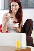 Happy woman eating breakfast — Stock Photo