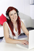 Woman with headphones working on laptop — Stock Photo