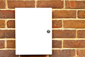 Locked white cupboard on a brick wall — Stock Photo