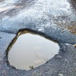 Deep, waterfilled pothole in the road - Stock Photo