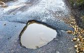 Profundo, waterfilled bache en el camino — Foto de Stock