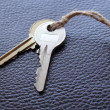 Two keys tied with string on black leather — Stock Photo #11575378