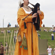 Girl in medieval dresses play bagpipes - Stockfoto
