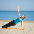 Cute young female practicing yoga on the beach — Stockfoto