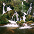 Serene waterfall cascades in wilderness - Stock Photo