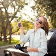Young woman shows the keys to her new car — Stock Photo