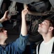 Two Car Mechanic repairing car - Stock Photo
