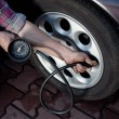 Tire pressure check - Stock Photo