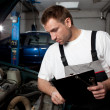 Auto mechanic checking car in service - Stockfoto