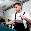 Stock Photo: Mechanic checking engine oil