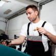 Mechanic checking engine oil - Stock Photo