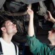 Car Mechanics repairing car - Stock Photo
